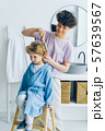 Young woman in pajamas combing small boys hair in bathroom smiling 57639567