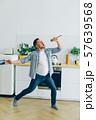 Man in casual clothing singing in spoon in kitchen dancing enjoying life 57639568