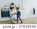 Loving mother giving lunch box to boy with school bag in kitchen smiling 57639590