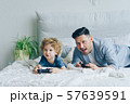 Father and child playing video game on bed at home pressing buttons on joystick 57639591