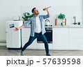 Portrait of playful middle-aged man singing in spoon in kitchen having fun 57639598
