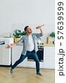 Portrait of silly guy having fun in kitchen singing in spoon dancing 57639599