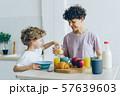 Happy family mother and son eating cereal with milk at home talking 57639603