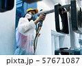 Powder coating of metal parts. A woman in a protective suit sprays white powder paint from a gun on 57671087