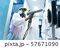 Powder coating of metal parts. A woman in a protective suit sprays white powder paint from a gun on 57671090