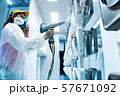 Powder coating of metal parts. A woman in a protective suit sprays white powder paint from a gun on 57671092