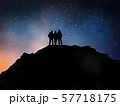 travelers on edge of mountain over night sky 57718175