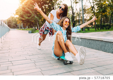 Two stylish excited girls have fun and skateboard 57718705