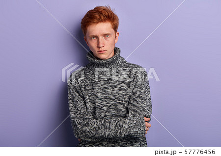 Freezing young man in gray warm sweater holding hands folded 57776456
