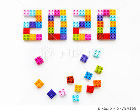 New 2020 Year. Colorful constructor blocks. Toy bricks lyingwithout order. Copy space among multicolored toy details. 57784169