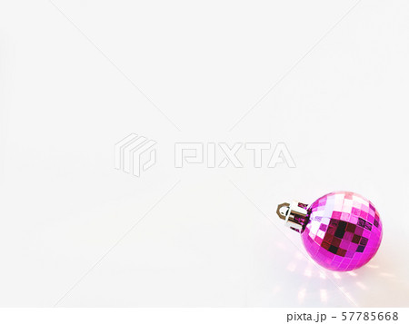 New Year background with magenta ball. Pink reflections, sunbeams on white copy space with decorative ball for Christmas tree. 57785668