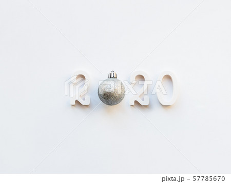 New Year 2020 background with silver ball. Numbers 2020 on white copy space with decorative ball for Christmas tree. 57785670