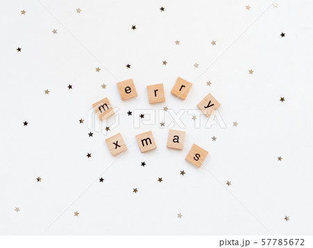 Christmas and New Year background with wooden words MERRY XMAS and star confetti. White copy space. 57785672