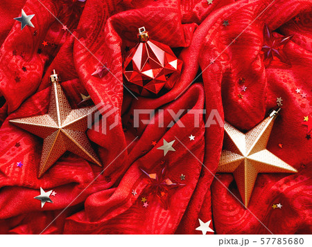 Bright red fabric with golden stars and ball. Star confetti on folded textile background. 57785680