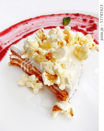 Carrot cake with popcorn sprinkles and raspberry jam. Tasty dessert on white plate. 57785923