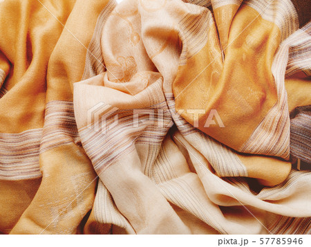 Pastel brown colored scarf. Folded beige warm accessory. Textile background. Top view, flat lay. 57785946