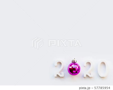 New Year 2020 background with purple ball. Numbers 2020 on white copy space with decorative ball for Christmas tree. 57785954