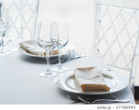 Table served for banquet with cutlery, wine glasses and napkins. Pastel colored decorations. 57786993