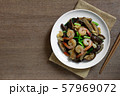 stir fried shiitake mushroom and shrimp with soy sauce in a ceramic dish on wooden table. 57969072