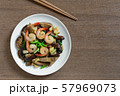 stir fried shiitake mushroom and shrimp with soy sauce in a ceramic dish on wooden table. 57969073