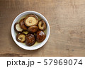 dried shiitake mushroom soaking with water in a bowl on wooden table prepare to cooking, top view. 57969074