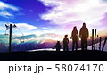 Family on a ski slope at sunset. 58074170