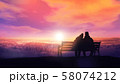 Couple on a bench looks at a winter sunset. 58074212