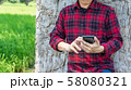 hand holding smartphone with green rice field. 58080321