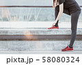 Young woman runner tying shoelaces 58080324