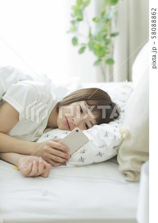 若い女性 ベッド スマホ 58088862