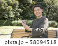 代々木公園で俳句を詠む中年男性 58094518