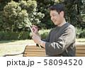 代々木公園で俳句を詠む中年男性 58094520