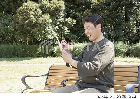 代々木公園で俳句を詠む中年男性 58094522