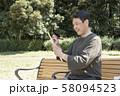 代々木公園で俳句を詠む中年男性 58094523