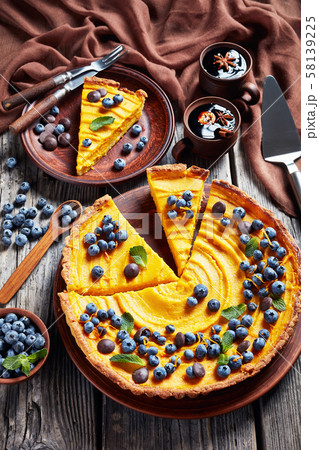 sliced pumpkin pie topped with fresh blueberries 58139225