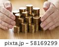 積み上げた金貨と手 58169299