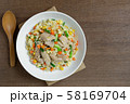 top view of fried rice with chicken and vegetables in a ceramic plate on wooden table. 58169704