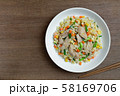 top view of fried rice with chicken and vegetables in a ceramic plate on wooden table. 58169706