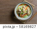 top view of stir fried japanese noodles with chicken and vegetables in a ceramic dish. 58169827