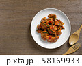 top view of stir fried chicken with red curry paste in a ceramic dish. 58169933