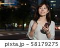 スマホを持つビジネスウーマン 丸の内 東京 都会 日本人女性 58179275