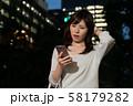 スマホを持つビジネスウーマン 丸の内 東京 都会 日本人女性 58179282
