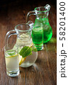 Different soft drinks in transparent jugs on a dark wooden background. menu for catering 58201400