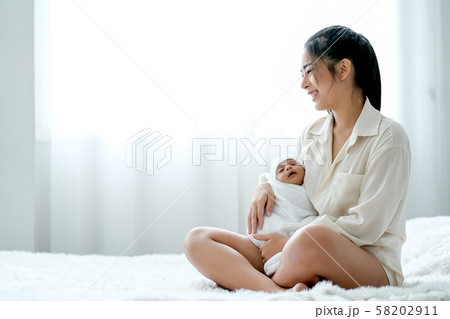 Asian mother hold her newborn baby, smiling and sit on the white bed 58202911
