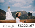Happy Asian tourist taking fun selfie at famous tourist attraction. Asia summer travel. Young woman taking mobile picture with phone at temple. 58222167