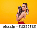 Beautiful young girl holding her adorable cat and looking at the camera 58222585