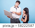 Caucasian male pointing at laptop and consulting with his asian wife 58222587