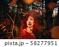 Woman in long red dress with deer horns in autumn forest. 58277951