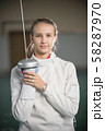 A young smiling woman fencer standing in the gym with a sword up 58287970
