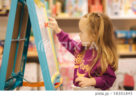 Adorable little girl draws on the desk in kids store 58301845